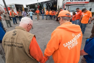 Samaritan's Purse volunteers begin the day with devotions and prayer before helping flood victims recover.