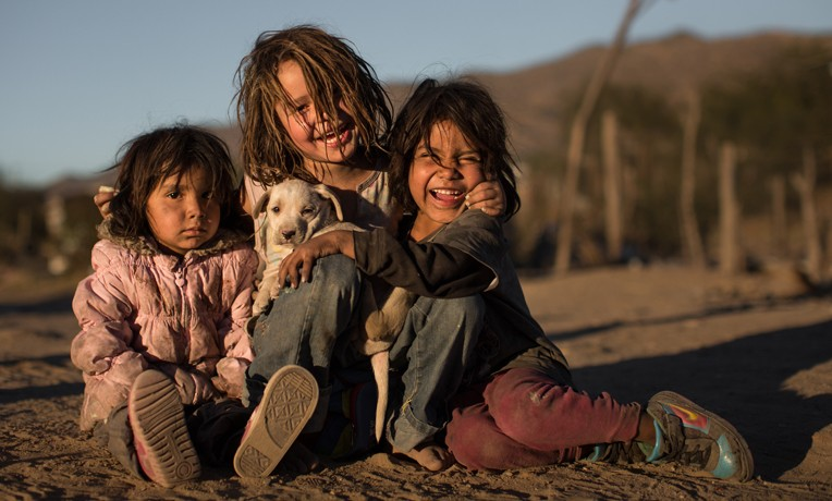 Children smiling with a dog near a community center built by Samaritan's Purse in Mexico. Hermosillo, Mexico, trash dump site