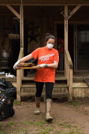 Samaritan's Purse volunteer Melissa Thompson carries a homeowner's belongings to the curb.