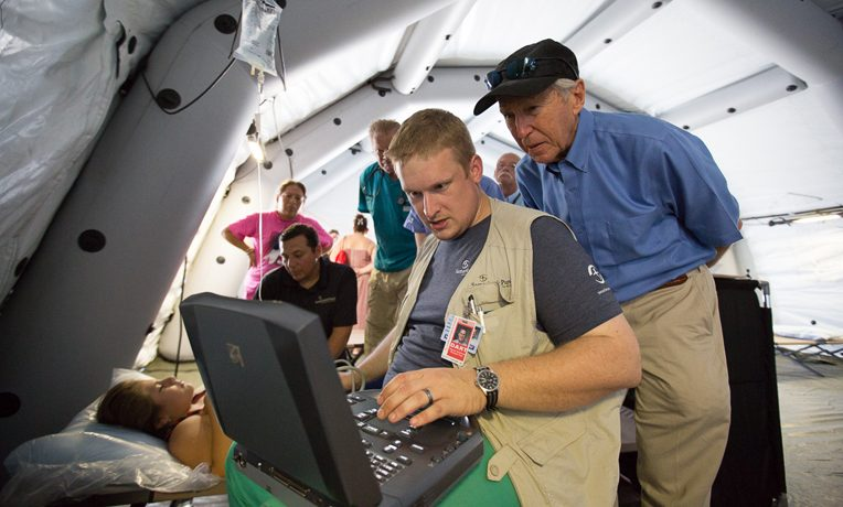 Samaritan's Purse relief; Dr. Richard Furman (background) observes as Dr. Elliott Tenpenny conducts an ultrasound at our emergency field hospital in Ecuador.