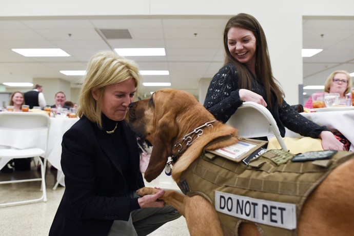 Danielle East watches as Greta Van Susteren shares a moment with Maggie, the service dog of Danielle's husband Elton, an Army veteran.