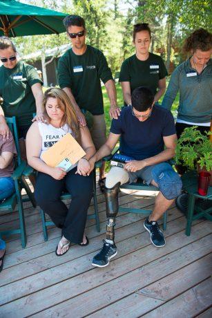 Charlie and Mandi Linville pray at the Friday fireside farewell at Samaritan Lodge Alaska.