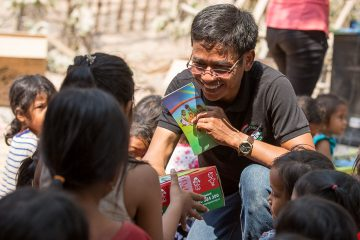 National Leadership Team Coordinator Sophea Sem distributes shoeboxes and The Greatest Gift Gospel booklet.