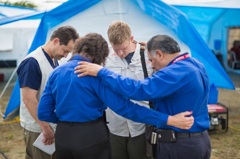 Lance Plyler (left) and Elliott Tenpenny (center) from Samaritan's Purse pray with chaplains from the Billy Graham Evangelistic Association outside of the emergency field hospital tents in Chone, Ecuador. Plyler and Tenpenny took turns managing the emergency field hospital over the past two months.
