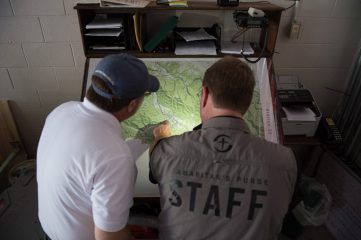 Samaritan's Purse staff examine flood-affected areas on a map of West Virginia.