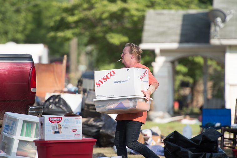 Homeowners are removing belongings from their flooded homes.