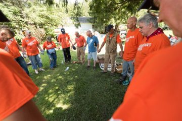 Volunteers and chaplains pray with Thomas Harris after completing work at his home.