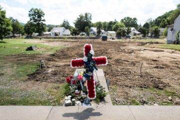 The remains of a home swept away by flooding are marked by a memorial to the residents who lived there.