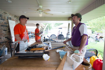 Mike Hawkins talks with Samaritan's Purse volunteers at his flooded home.