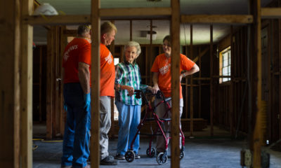 Elderly woman stands with volunteers in her gutted home. post-flooding Baton Rouge homeowner, widow, grandmother