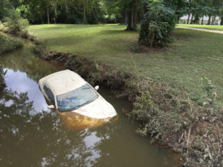 Flooded car in drainage ditch