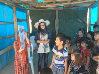 Boys and girls displaced from Mosul listen intently to a hygiene presentation during one of the center's mobile clinic visits.