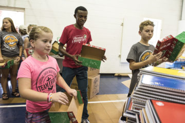Faith, Alex, and Griffin kick off the shoebox packing.