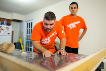 Ryan Reilly and Diego Acosta make sure the kitchen cabinets are ready to be installed.