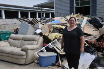 Sonia stands in front of soaked belongings from her parents' home.