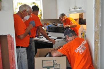Volunteers removing kitchen appliances