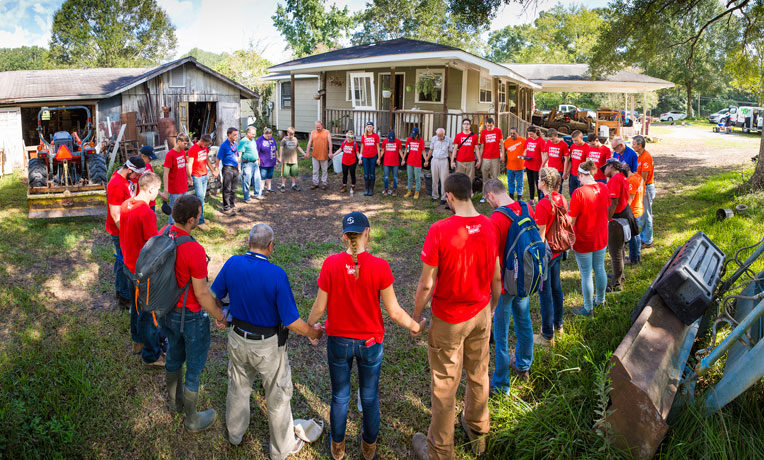 Liberty students praying with homeowners
