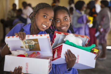 Two girls holding their shoebox gifts