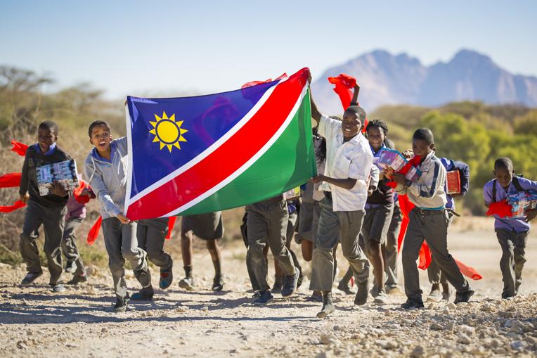 Children holding the national flag.