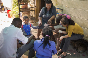 In Namibia, Engela (center) pray with the children under her care.