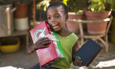 A young boy in Namibia receives an Operation Christmas Child shoebox that contains a Bible