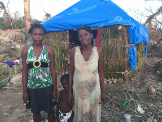 Women stand in front of a shack with blue plastic covering the roof. Tarps from Samaritan's Purse are being put to good use in southern Haiti.