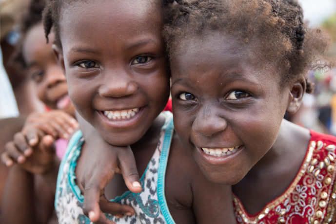 The hurricane did not wash away the smiles of Haitian children. Two young girls smiling.