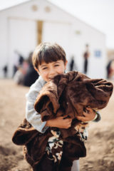 Ammar and Muna's oldest son holds a blanket from Samaritan's Purse.