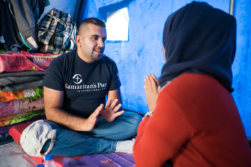 Janan speaks with a recently displaced family in their tent.