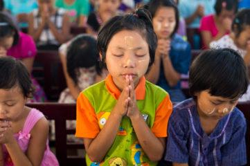 Children praying during a shoebox distribution in Myanmar.