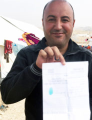 Ammar holds a copy of the ISIS sentencing—55 lashes—that was given to him and his relatives. This copy was his cousin's and the Arabic has been blurred for security.