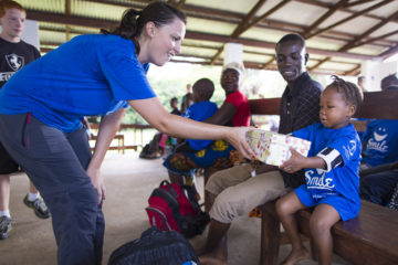 Daniela Spevak hands Moses an Operation Christmas Child shoebox gift.
