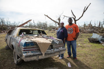 The Randles stand with the car that played an important role during the night that the tornado hit.