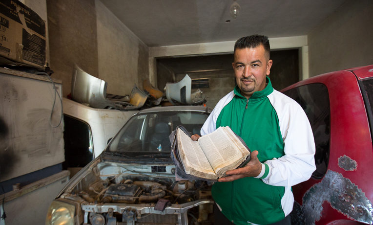 Román still has the Bible he received 17 years ago in prison. Roman now works in an auto repair garage and is involved in ministry through a local church.