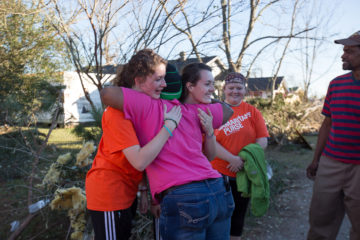 Homeowner Youlunda Michel hugs students from William Carey University.