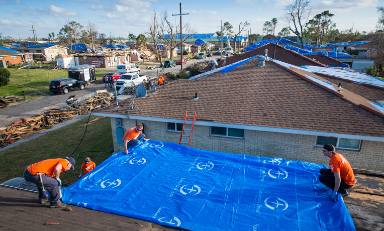 Working on covering roofs damaged by a tornado in New Orleans--Samaritan's Purse volunteers