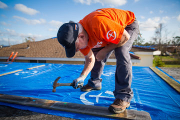 Volunteers are covering roofs with our signature heavy-duty plastic sheeting.