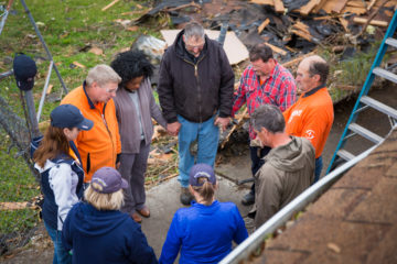 Our team prays with April Jenkins at her home, which was badly damaged by the recent tornado.
