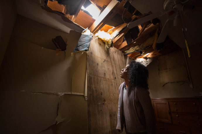 April Jenkins looks through a hole in the roof of her son's bedroom.