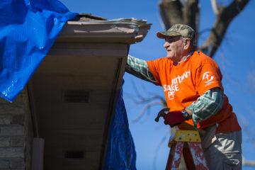 Sam worked hard tarping roofs.