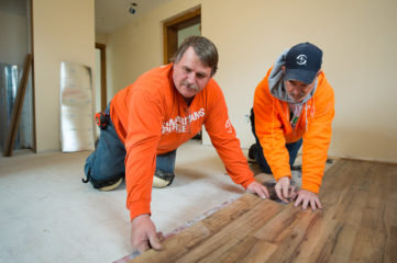 Phillip O'Dell—whose house was repaired by Samaritan's Purse—joins Roland Macey in laying flooring.