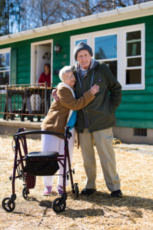 James and Arbutus Sams embrace in front of their West Virginia home.