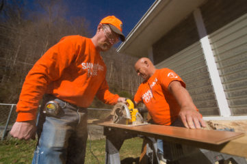 Jerry Kilby and Thomas Schardt cut flooring on a cloudless West Virginia morning.
