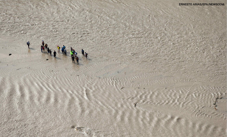 Aerial photograph shows a group of people asking for help as they are cut off due to the flooding of the Viru River, which destroyed several bridges connecting various villages in the northern region of La Libertad, Peru.