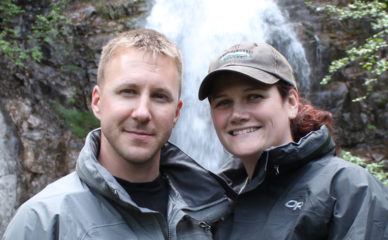 Drew and Misty Toothman enjoyed their time in Alaska and brought back a stronger marriage. Picture of them in front of waterfall near lake.