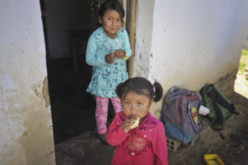 Sisters eat bread baked in an oven provided by Samaritan's Purse.