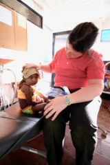 Nurse Kate Mach cares for the 3-year-old with a high fever.
