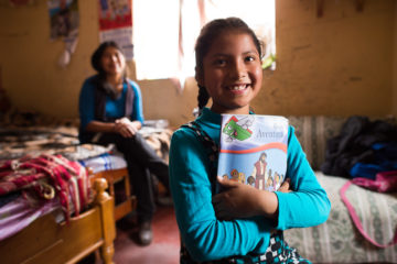 In her room, Paola hugs her student booklet for The Greatest Journey.