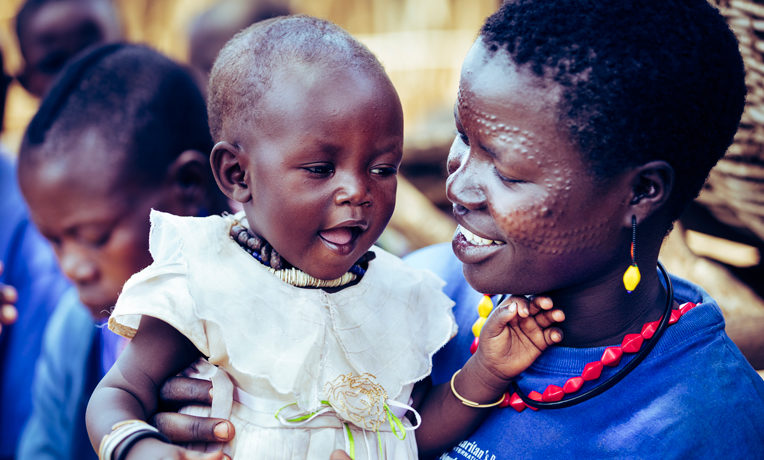 Leader Mother Kalian Lorot plays with one of her five children in Uganda.