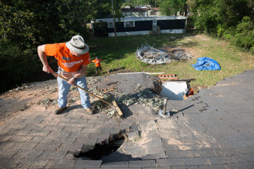 Gary Ellington, a member of Williamsville Baptist Church in Kosciusko, Mississippi, which is housing our volunteers, clears debris from a hole in a roof before tarp is attached.